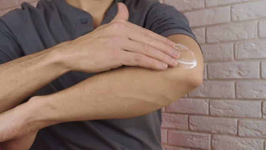 Rubbing ointment on arm
